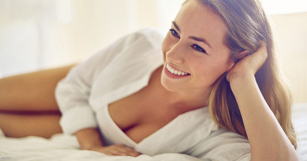 A woman is happy with her results after receiving breast augmentation.