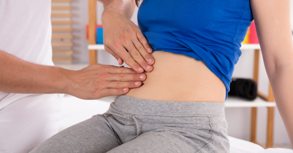 A woman's abdomen is examined in her tummy tuck consultation.